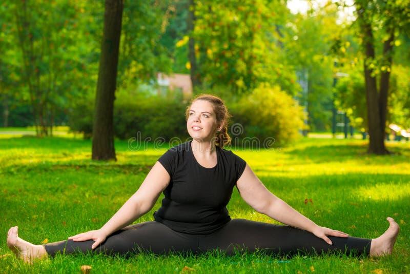 flexível de tamanho grande da mulher feliz esticado em um assento do gramado imagem de stock