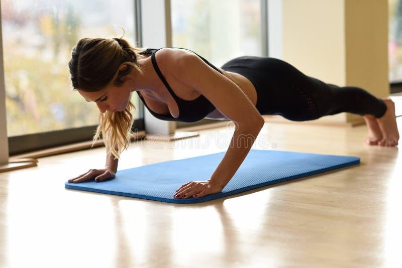 Flexões de braço bonitas novas do doin da mulher no gym foto de stock