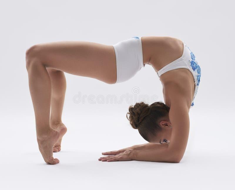 Flexibel meisje die terwijl het doen van acrobatische stunt stellen royalty-vrije stock foto