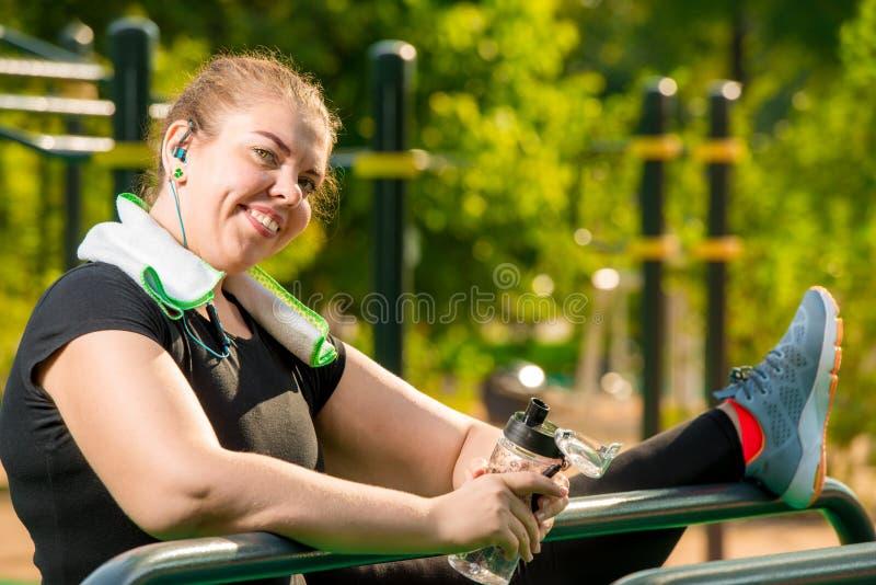 flexibel plus grootte nam de vrouw met een haven op de speelplaats in dienst in een park royalty-vrije stock foto