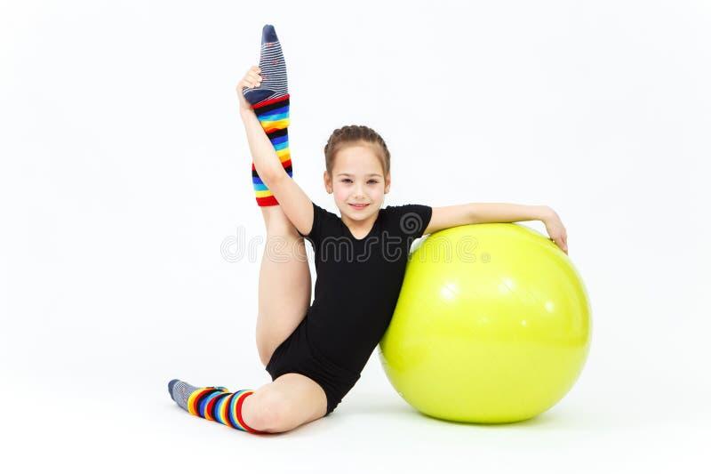 Flexibel tienermeisje die gymnastiekoefeningen op geschiktheidsbal doen stock afbeeldingen