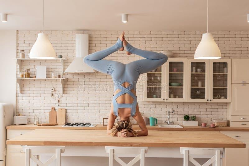 Flexibele en sterke jonge yogameester die haar opmerkelijke vaardigheden tonen stock foto