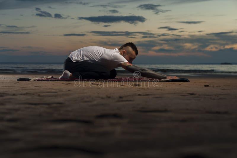 Flexibele jonge mens met tatoegeringen die yoga doen openlucht royalty-vrije stock fotografie
