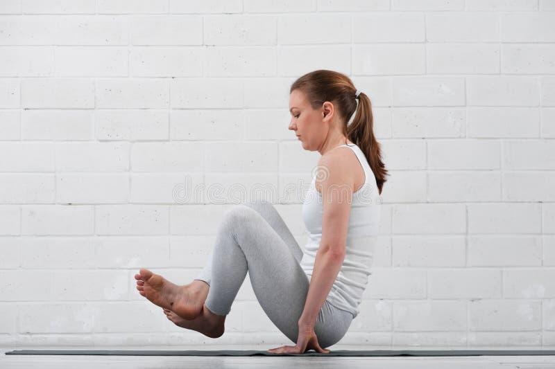 Flexibele vrouw die yoga op hoog niveau binnen uitoefenen stock afbeeldingen