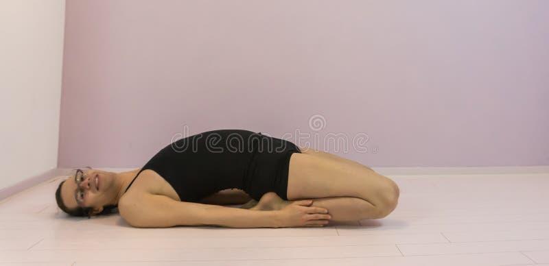 Flexibiliteit opleiding, die quadriceps in de hogere benen uitrekken, LGBT-transsexueelmeisje het uitwerken stock afbeelding