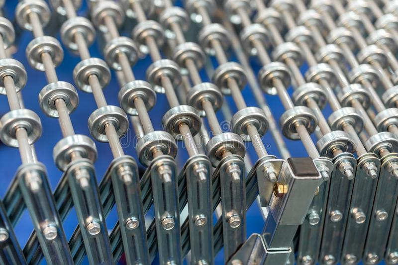 Flexible adjustable roller conveyor. Poratable innovative product`s transportation technology for factory and logistic. Company royalty free stock image