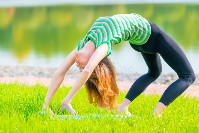 Flexible athlete makes a bridge. In nature stock photos