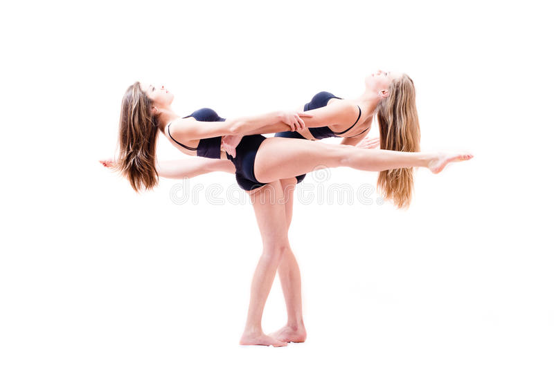 2 flexible athletic woman pretty girl friends showing performance holding hands have raised legs parallel to the floor. Two flexible athletic women pretty girl stock photo