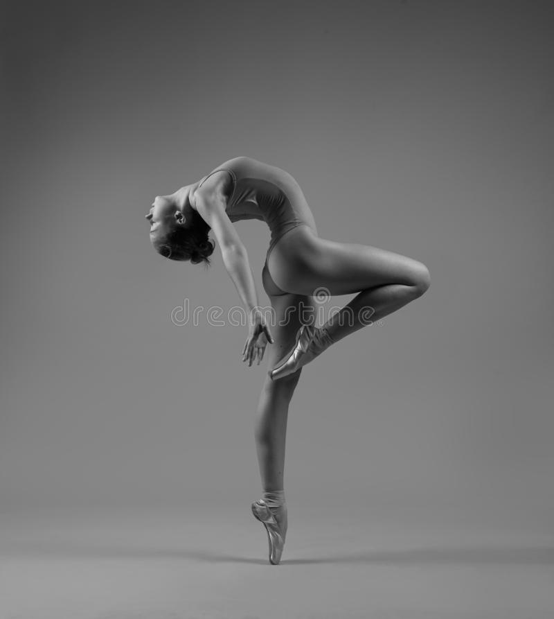 Flexible ballerina in pointe bends back stock photo