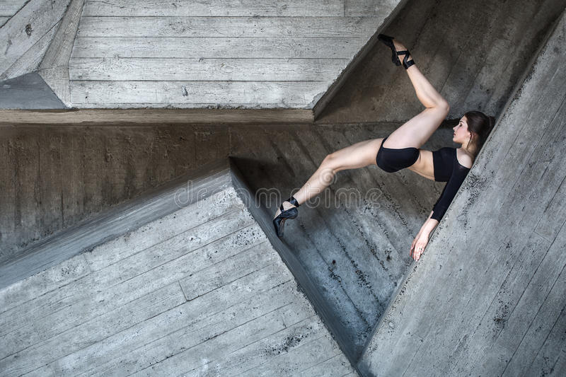 Flexible dancer posing. Lies between the complex geometry of concrete walls. Dancer lying on his back resting his toes in the opposite wall. The girl in black royalty free stock images