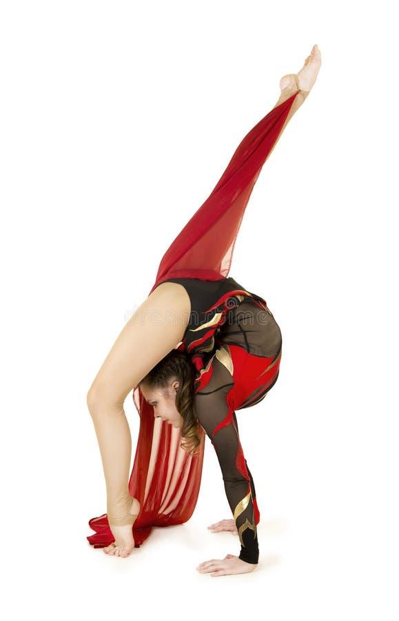 Flexible equilibrist performs exercises on acrobatic walking sticks. Studio photo on white background, isolated image stock photos