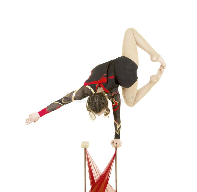 Flexible equilibrist performs exercises on acrobatic walking sticks. Studio photo on white background, isolated image stock photo