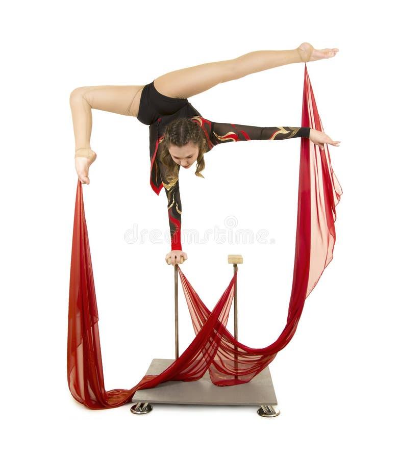 Flexible equilibrist performs exercises on acrobatic walking sticks. Studio photo on white background, isolated image royalty free stock photos