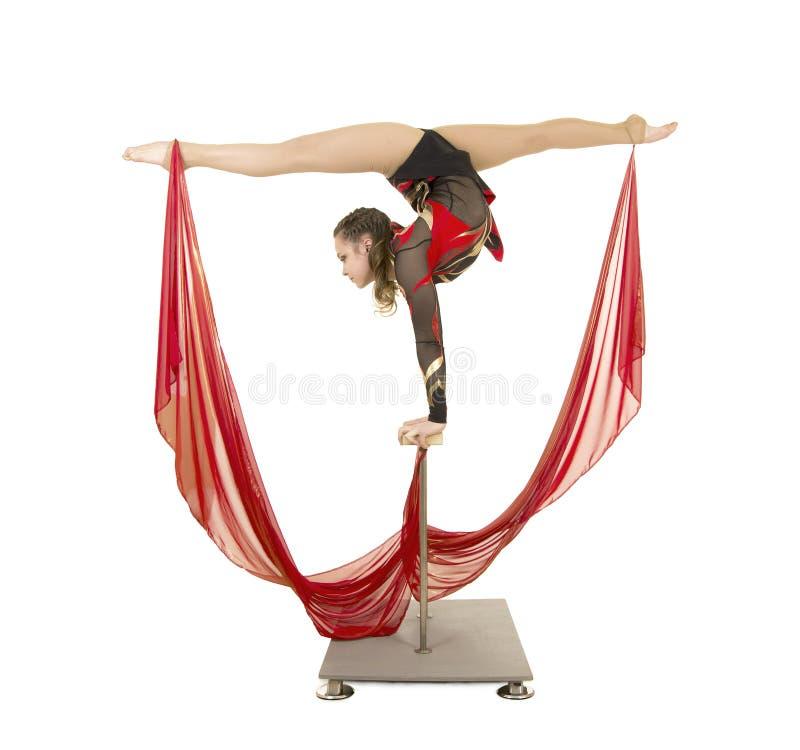 Flexible equilibrist performs exercises on acrobatic walking sticks. Studio photo on white background, isolated image stock image