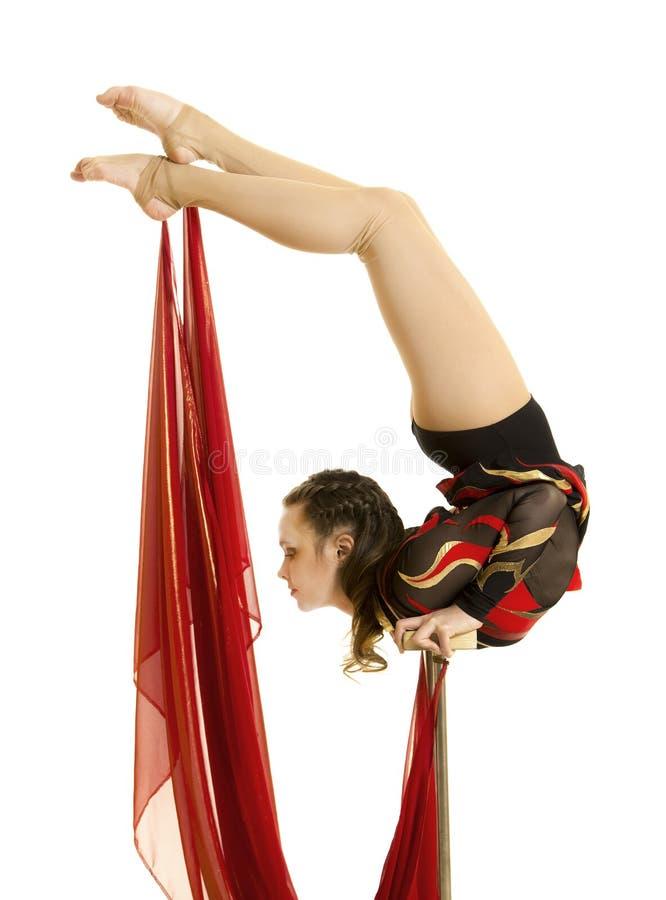 Flexible equilibrist performs exercises on acrobatic walking sticks. Studio photo on white background, isolated image royalty free stock photography
