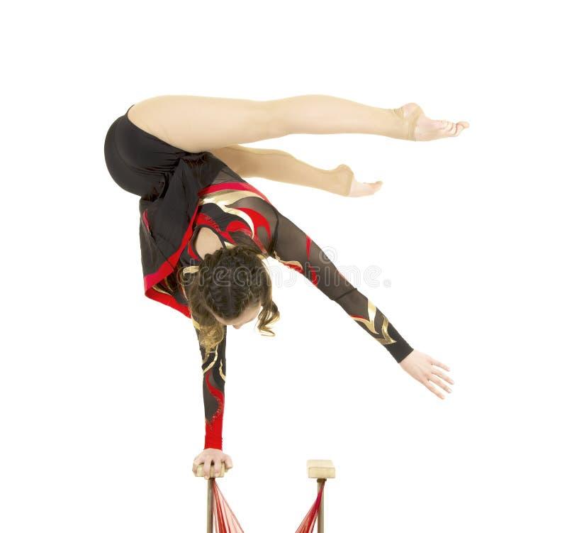 Flexible equilibrist performs exercises on acrobatic walking sticks. Studio photo on white background, isolated image royalty free stock image