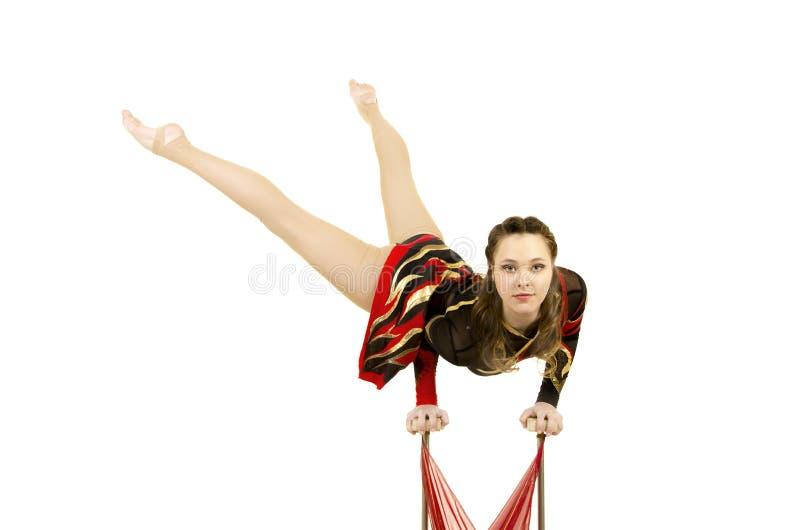 Flexible equilibrist performs exercises on acrobatic walking sticks. Studio photo on white background, isolated image stock photography