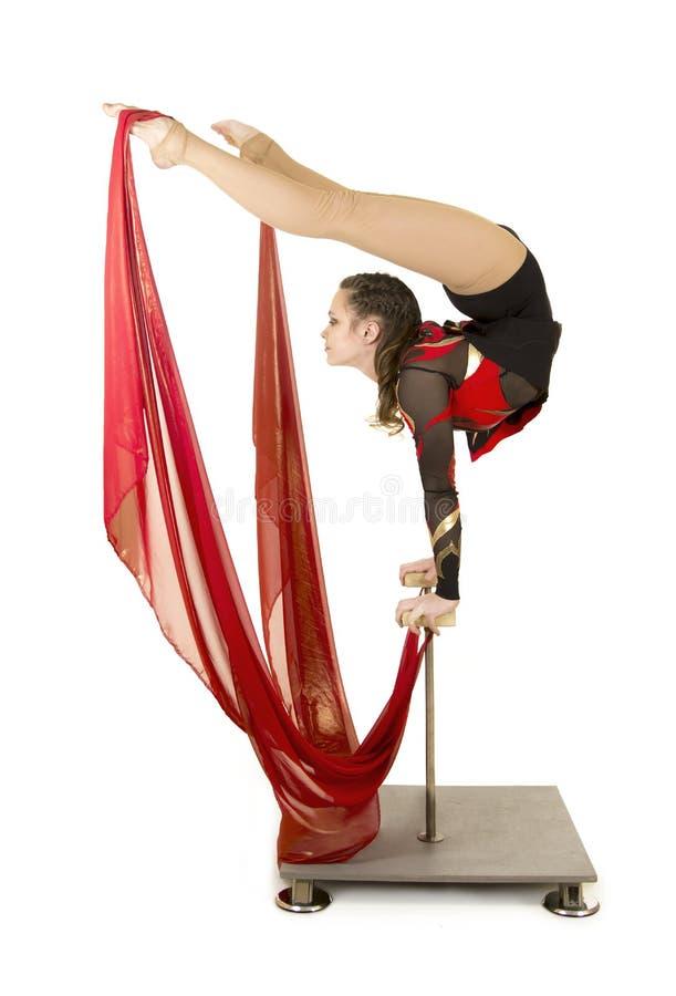 Flexible equilibrist performs exercises on acrobatic walking sticks. Studio photo on white background, isolated image royalty free stock photo