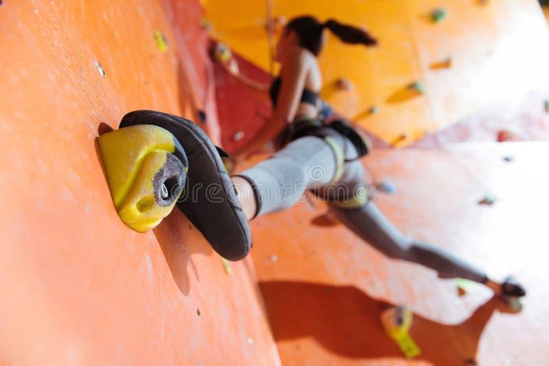 Flexible Frau, die stark in kletternder Turnhalle ausbildet stockbilder