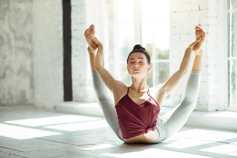 Flexible girl doing yoga posture in a gym stock photos