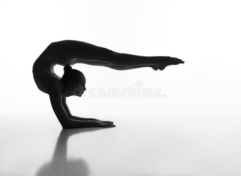 Flexible girl makes a beautiful pose b&w. Flexible girl does a beautiful pose in the studio in the backlight royalty free stock images
