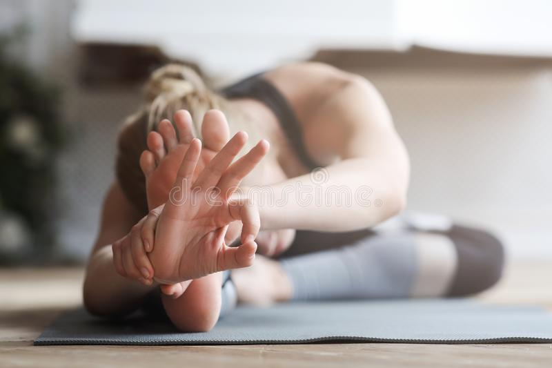 Flexible girl stretching at home, touching her knees with forehead. Sporty girl stretching during yoga ptacrice at home, showing ok sign, flexible body concept stock photos