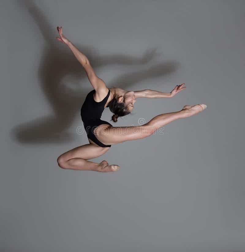 Flexible gymnast. Girl makes an expressive jump. Flexible gymnast in black lingerie. Girl makes an expressive jump royalty free stock photos