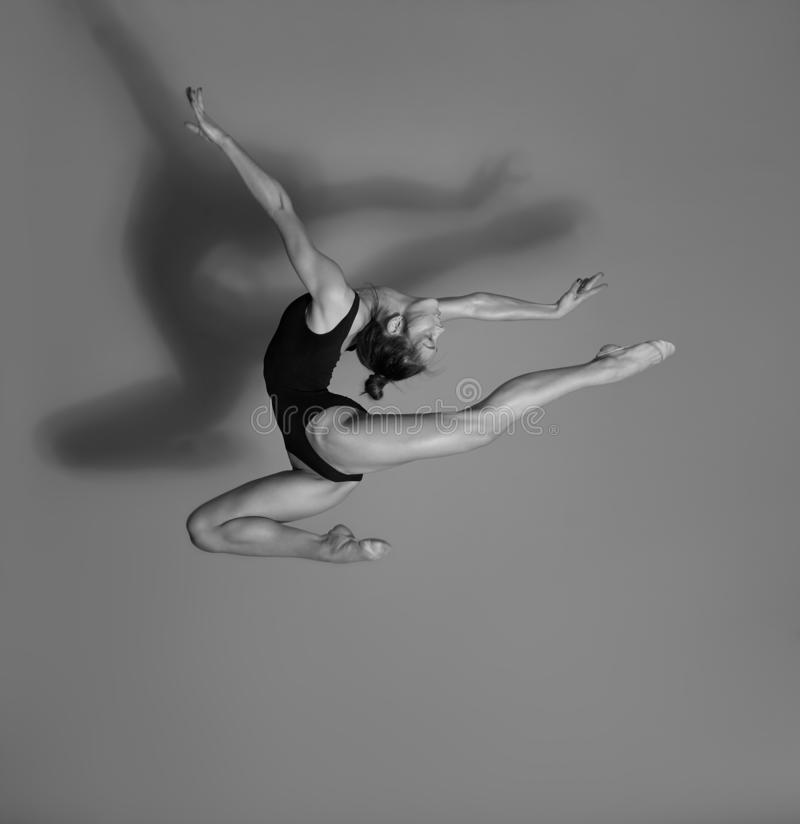 Flexible gymnast. Girl makes an expressive jump. Flexible gymnast in black lingerie. Girl makes an expressive jump stock image