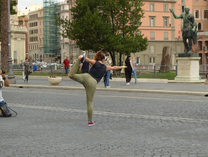Flexible hipster girl balances in a standing pose, bending her leg back. Posing for a photo shoot in front of the royalty free stock photo