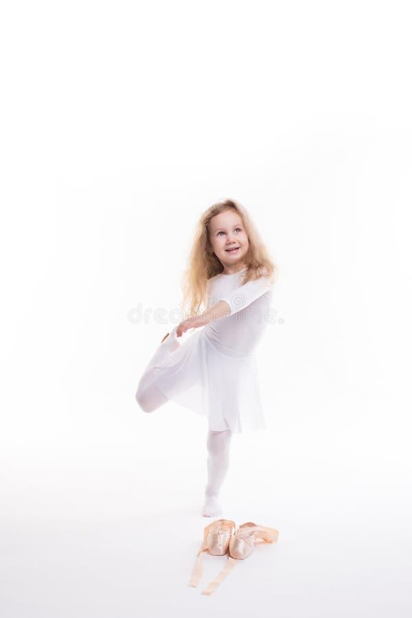 Flexible little girl ballerina doing gymnastic exercises. royalty free stock photos