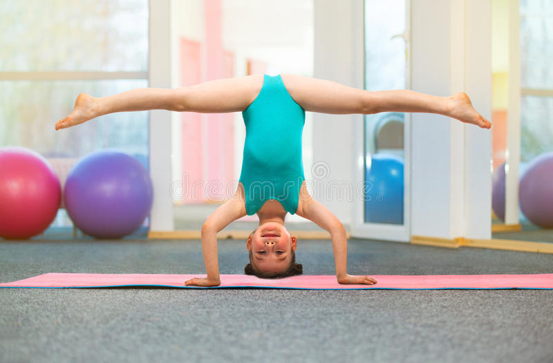 Flexible little girl gymnast standing on head in gym. Sport, training, fitness, yoga, active lifestyle concept stock image