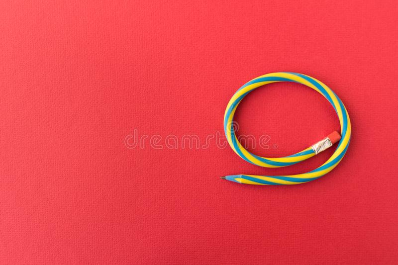 Flexible pencil . Isolated on red background. Bending pencil.  stock photo