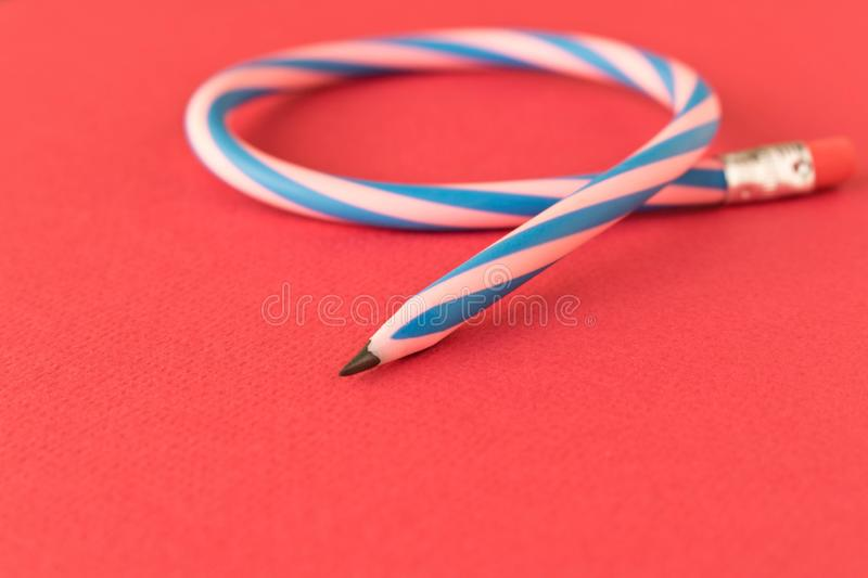 Flexible pencil . Isolated on red background. Bending pencil.  royalty free stock images