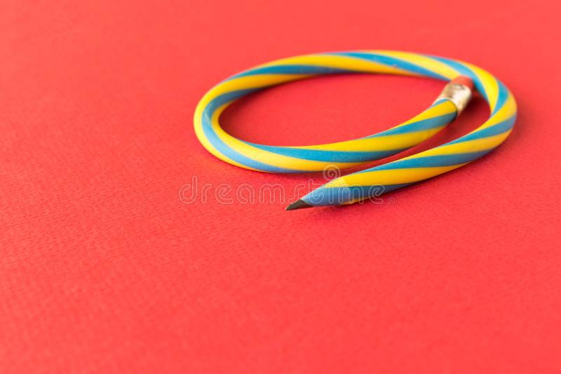 Flexible pencil . Isolated on red background. Bending pencil.  royalty free stock photography