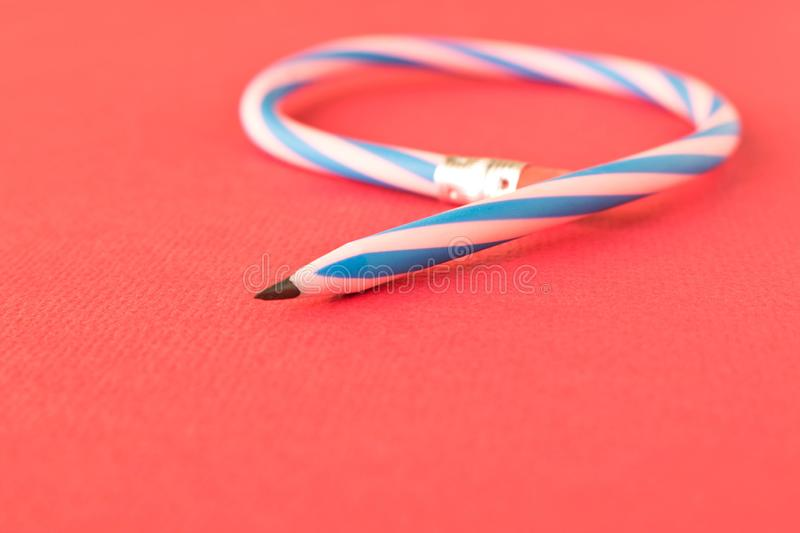 Flexible pencil . Isolated on red background. Bending pencil.  stock images