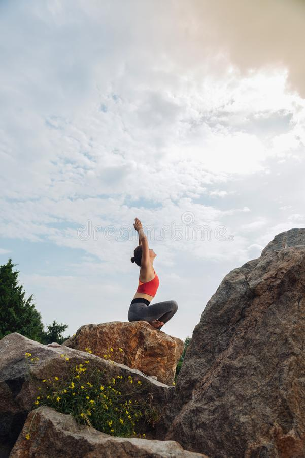Flexible slim woman lifting her hands while doing yoga. Flexible and slim. Flexible and slim woman lifting her hands while doing yoga sitting on rock around stock photography