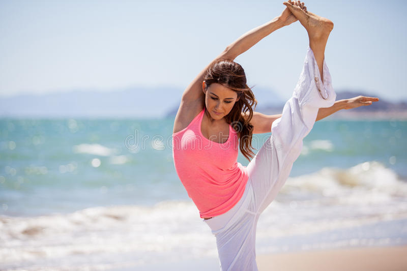 Flexible woman doing some yoga. Cute Latin brunette lifting her leg for a yoga pose at the beach royalty free stock photo