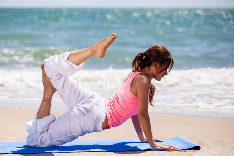 Flexible woman doing yoga. Beautiful young woman trying out a yoga pose on a sunny day at the beach royalty free stock image