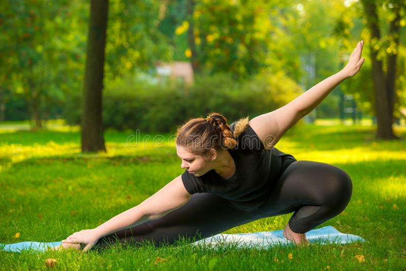 Flexible woman plus size in the park on the lawn performs stretching. Exercises stock images