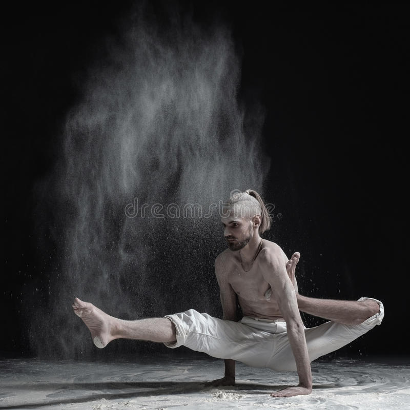 Flexible yoga man doing hand balance asana brahmachariasana. Dust flying in air royalty free stock photography