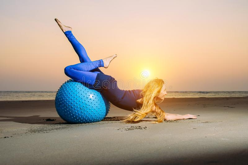 Flexible young girl with long blonde hair exercising on a yoga ball. Gymnast woman and big sports ball in the evening light. On the beach royalty free stock images
