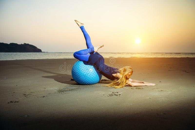 Flexible young girl with long blonde hair exercising on a yoga ball. Gymnast woman and big sports ball in the evening light. On the beach royalty free stock photography