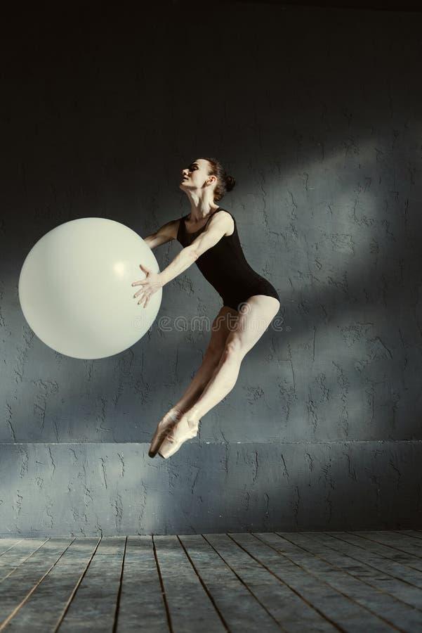 Flexibler charismatischer Turner, der unter Verwendung des weißen Ballons durchführt lizenzfreie stockfotos