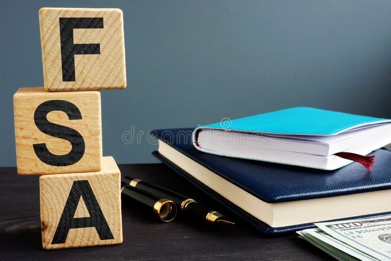 Flexibles Ausgabenkonto FSA geschrieben auf hölzerne Würfel lizenzfreie stockbilder
