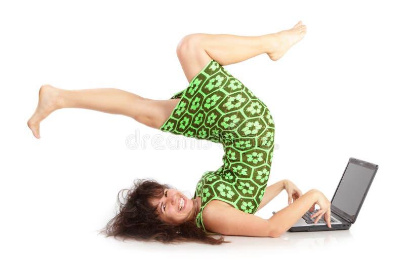 Flexibles schönes Mädchen mit dem Laptop auf einem Weiß lizenzfreies stockfoto