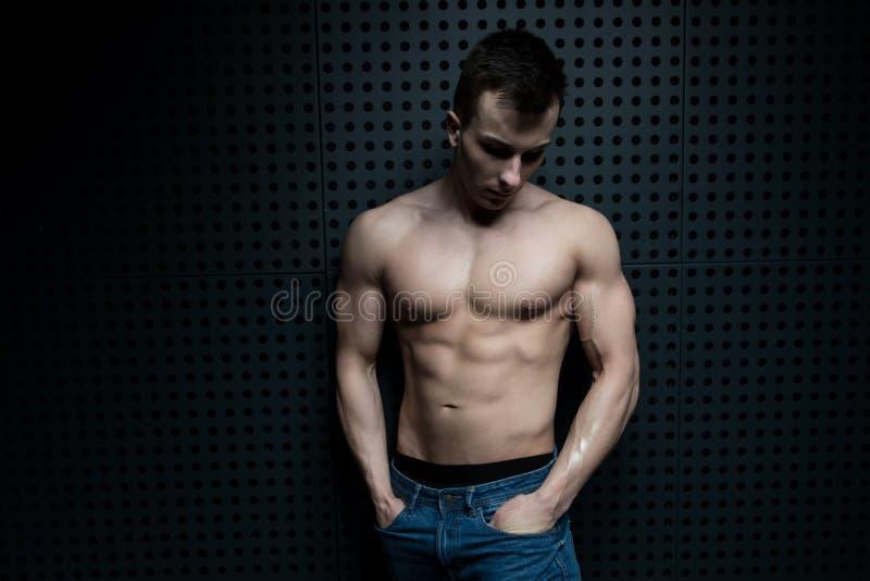 Flexing Muscles Against modelo a parede fotos de stock