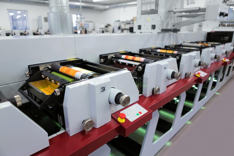 Flexographic printing machine with an ink tray, ceramic anilox roll, doctor blade and a print cylinder with polymer relief plate. Flexographic printing machine stock photo