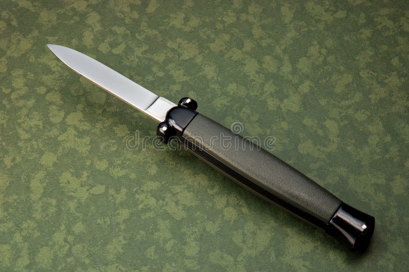 Flick knife. On green camouflage background from above royalty free stock photo