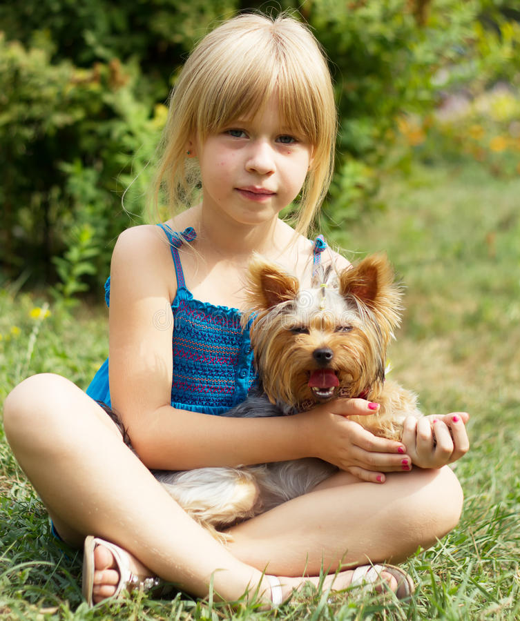 Flicka 6 år gammalt sammanträde på gräset med Yorkshire Terrier arkivfoto