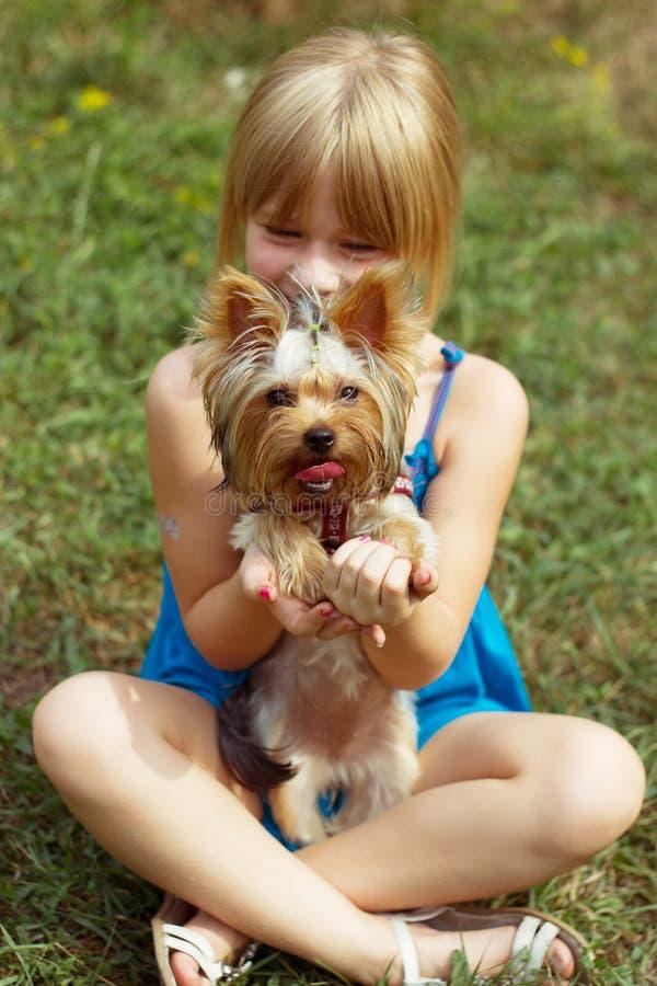 Flicka 6 år gammalt sammanträde på gräset och hållna Yorkshire Terrier royaltyfri foto
